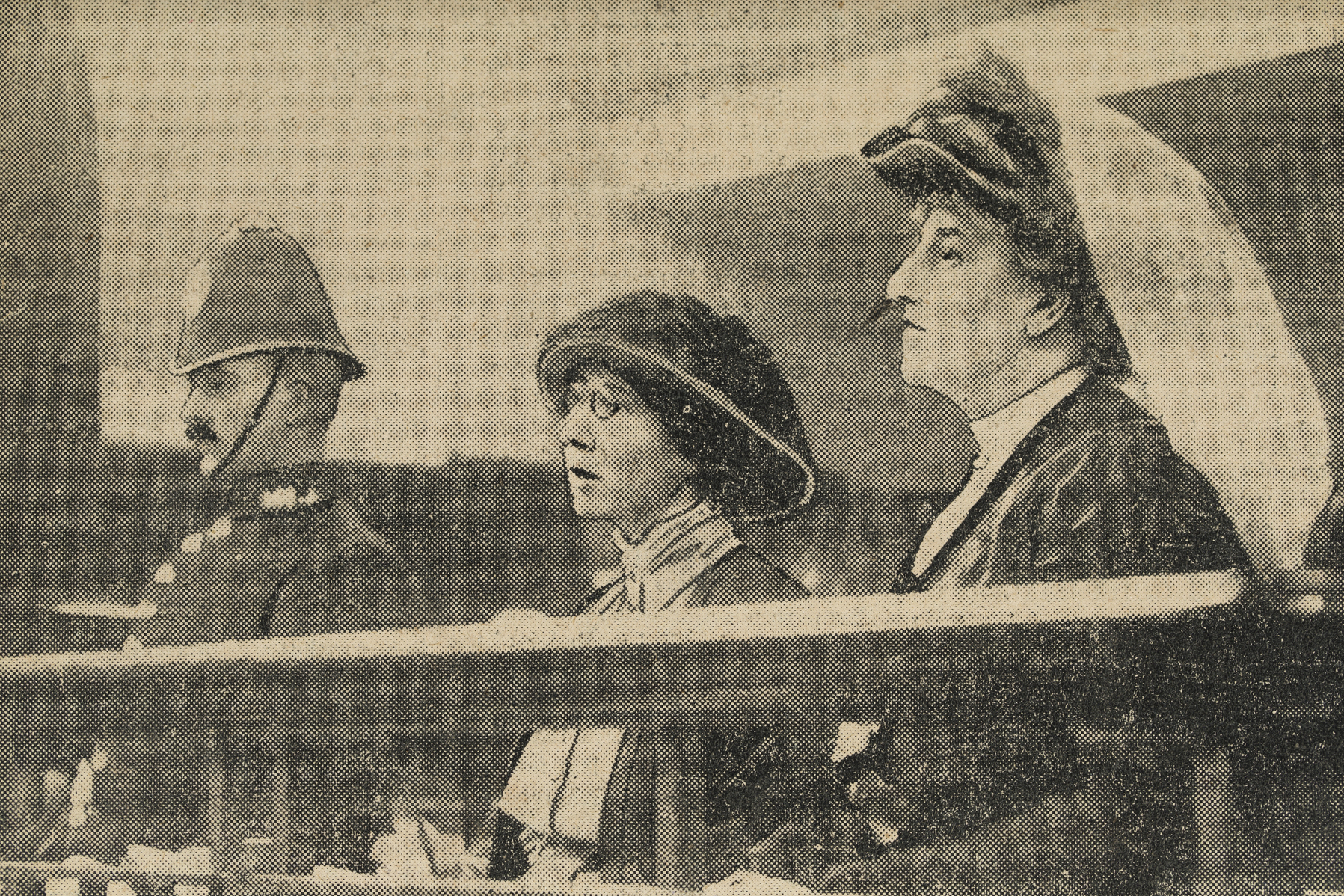 Photograph of Ethel Moorhead and Dorothea Smith in court. At the far left is a policeman, in the middle is Moorhead and at the far right is Smith.